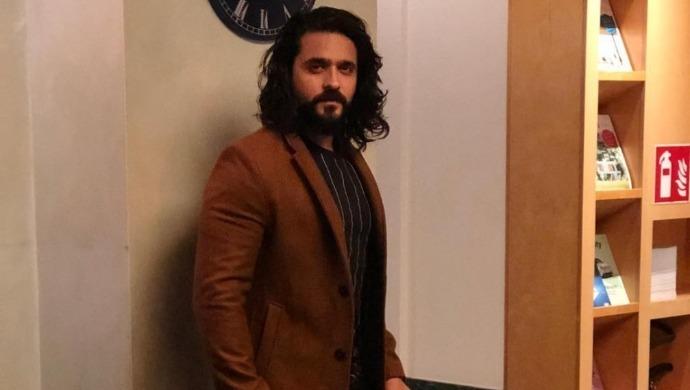 Ashish Sharma strikes a pose in a brown coat