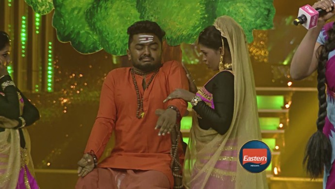 Jasim comes on stage dressed up as a 'sami' to provide background visuals for Swetha's song