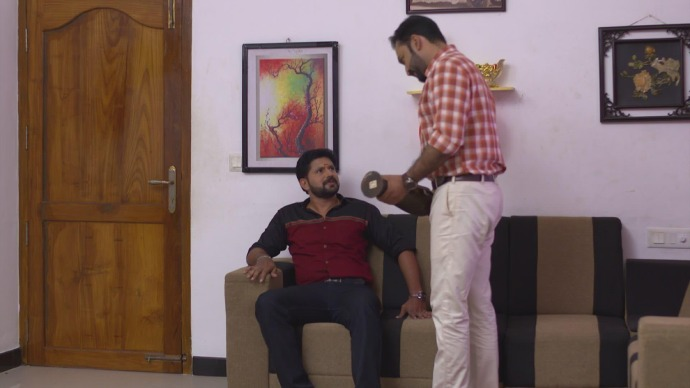 Anand hits Subru's leg with a flower vase