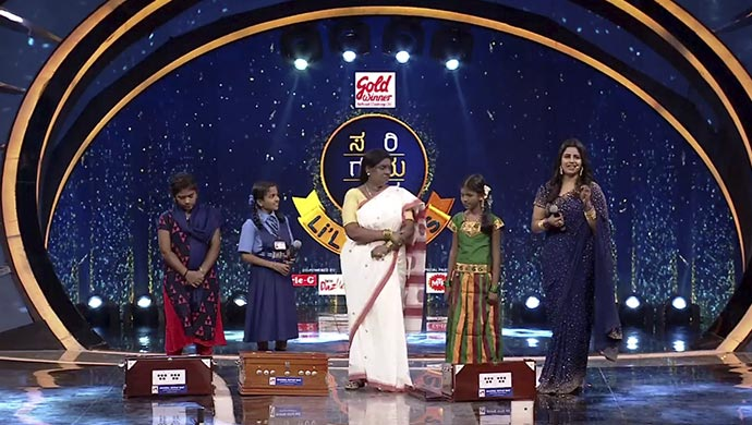 A Still Of Mahaguru's Wife Gifting The Contestants Harmonium To Support Their Musical Dream