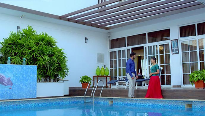 A Still Of Aditya And Paaru Talking By The Pool