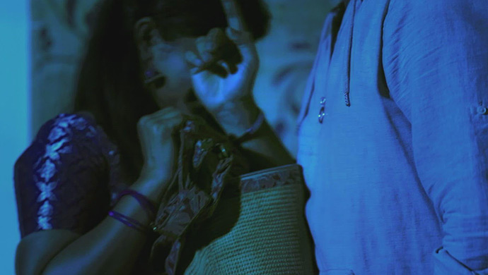 A Still Of The Coin Slipping From Krishna's Hand And Falling Into Radha's Bag