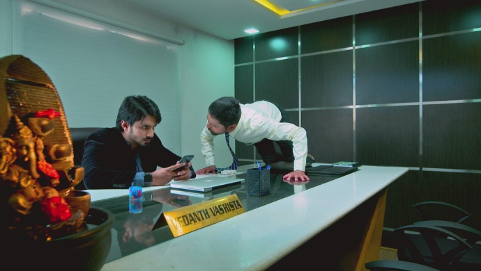 A Still Of Vedanth And Kantha Standing On His Desk